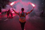 A striking railway worker holds flares during a demonstration in Marseille, southern France, Friday, Jan. 24, 2020. French unions are holding last-ditch strikes and protests around the country Friday as the government unveils a divisive bill redesigning the national retirement system. (AP Photo/Daniel Cole)