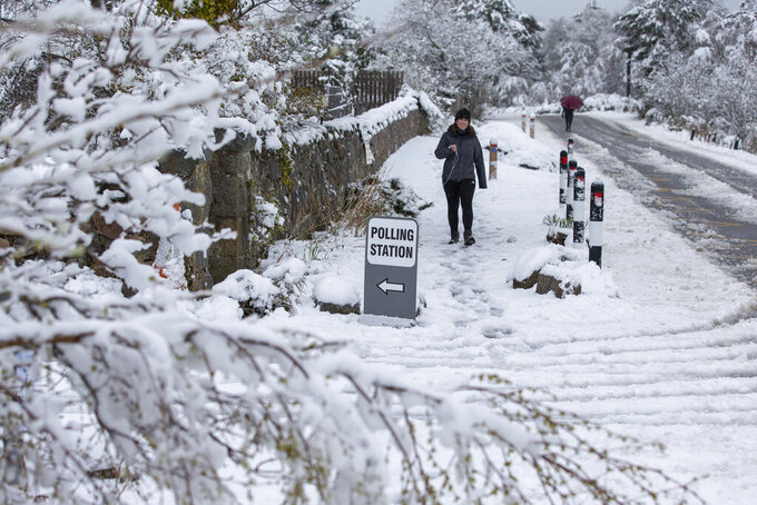 A woman arrives at a polling station, after snowfall, in the village of Farr, near Inverness, Scotland, Thursday May 6, 2021. Scots are heading to the polls to elect the next Scottish Government - though the coronavirus pandemic means it could be more than 48 hours before all the results are counted. (Paul Campbell/PA via AP)