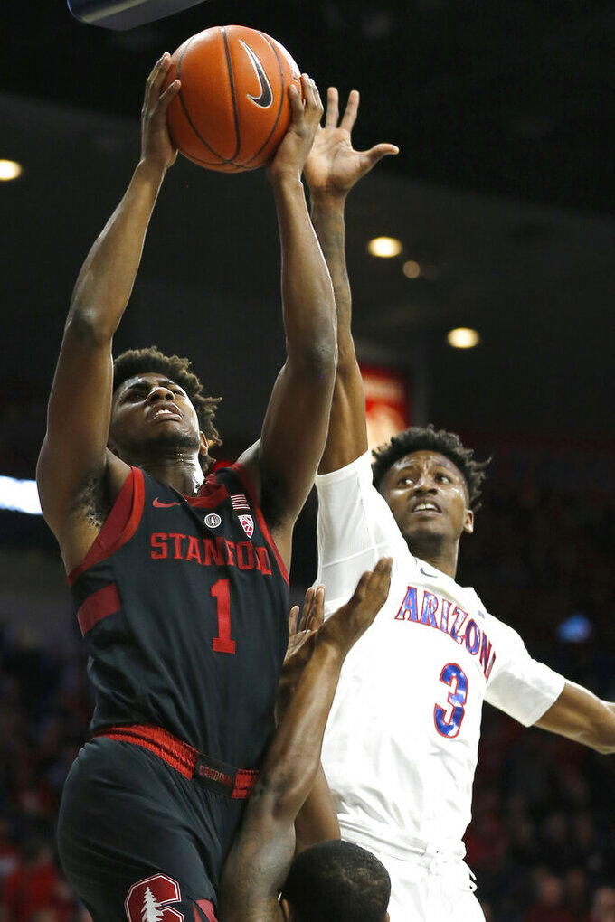 Stanford guard Daejon Davis (1) drives past Arizona guard Dylan Smith in the first half during an NCAA college basketball game, Sunday, Feb. 24, 2019, in Tucson, Ariz. (AP Photo/Rick Scuteri)