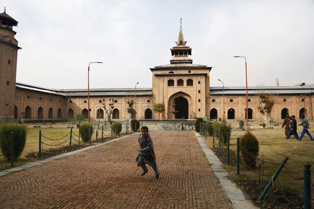 A Kashmiri boy plays outside Jamia Masjid in Srinagar, Indian controlled Kashmir, Wednesday, Dec. 18, 2019. A call to afternoon prayer has rung out from the central mosque in disputed Kashmir's largest city for the first time in more than four months, ending a virtual ban on religious practice in the Muslim-majority region's biggest mosque. The Jamia Masjid was shut Aug. 5 as part of India's security lockdown after Prime Minister Narendra Modi's Hindu nationalist-led government stripped Kashmir of its semi-autonomous status. (AP Photo/Mukhtar Khan)