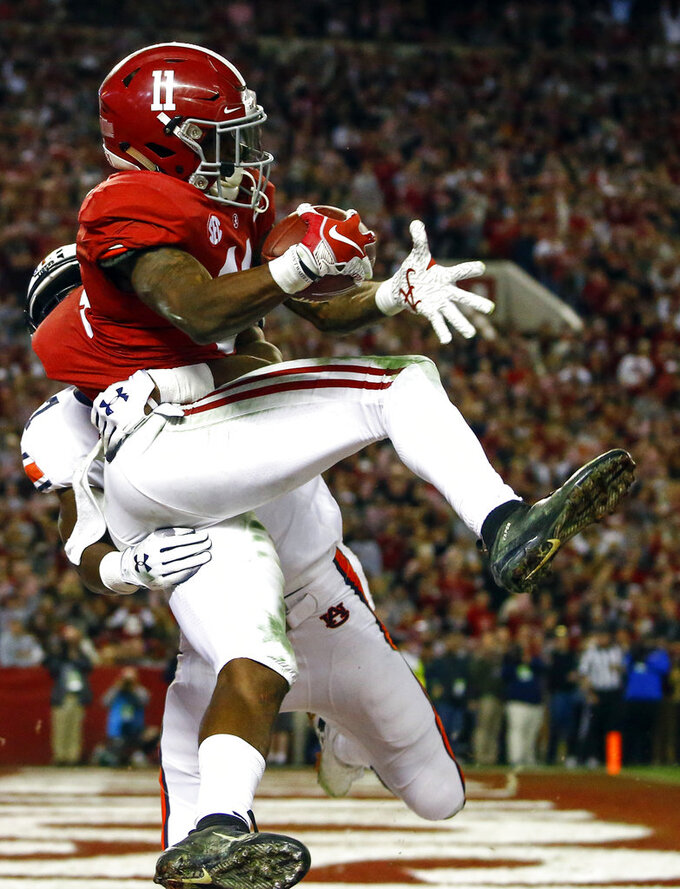 Alabama wide receiver Henry Ruggs III (11) catches a pass over Auburn defensive back Roger McCreary (17) for a touchdown during the second half of an NCAA college football game, Saturday, Nov. 24, 2018, in Tuscaloosa, Ala. (AP Photo/Butch Dill)