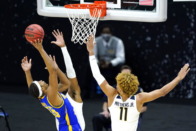 Morehead State's Ta'lon Cooper (55) shoots against West Virginia's Emmitt Matthews Jr. (11) during the second half of a college basketball game in the first round of the NCAA tournament at Lucas Oil Stadium Saturday, March 20, 2021, in Indianapolis. (AP Photo/Mark Humphrey)