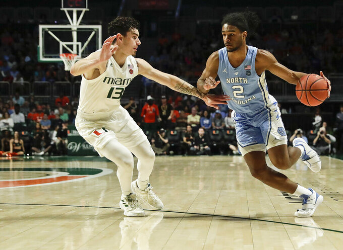 North Carolina guard Coby White dribbles the ball against Miami guard Anthony Mack during the first half of an NCAA college basketball game on Saturday, Jan. 19, 2019, in Coral Gables, Fla. (AP Photo/Brynn Anderson)