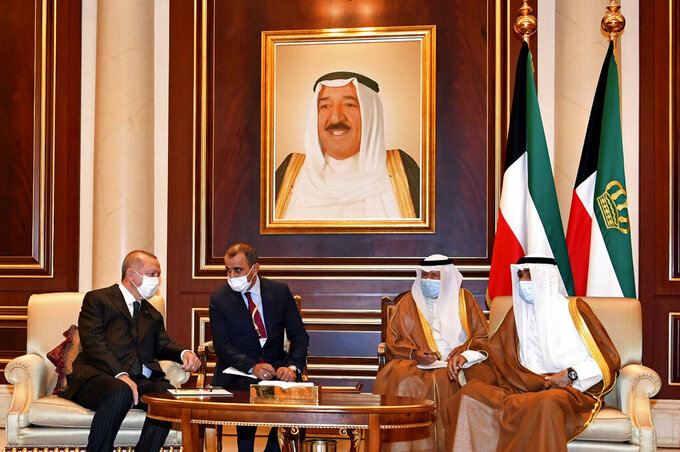 In this photo released by Kuwait News Agency, KUNA, Turkish President Recep Tayyip Erdogan, left, talks to Sheikh Nawaf al-Ahmad al-Sabah, the new Emir of Kuwait, right, in Kuwait, Wednesday, Oct. 7, 2020. The new emir replaced his half-brother, the late ruler Sheikh Sabah al-Ahmad al-Jaber al-Sabah, seen in portrait, who died in the United States at the age of 91 last month.  (KUNA via AP)