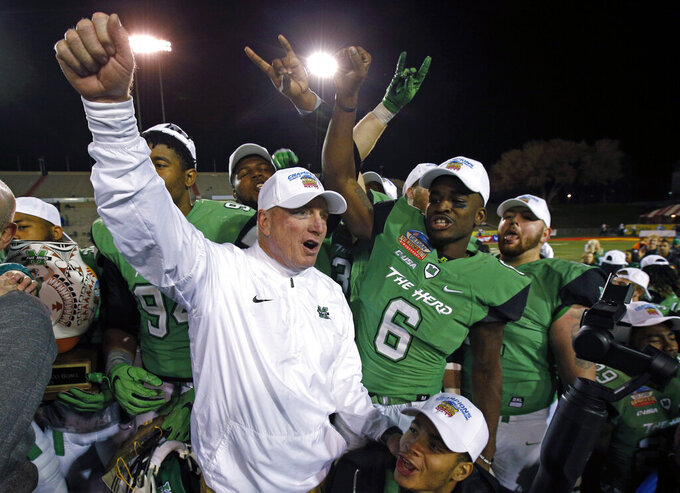 RETRANSMISSION TO CORRECT TO EAST DIVISION - FILE - In this Dec. 16. 2017, file photo, Marshall players and coach Doc Holliday celebrate after their 31-28 victory over Colorado State in the New Mexico Bowl NCAA college football game in Albuquerque, N.M. Marshall goes into Holliday's 10th season as the favorite in Conference USA's East Division. The Thundering Herd won four of their final five games last season, including their seventh consecutive bowl victory. (AP Photo/Andres Leighton, File)