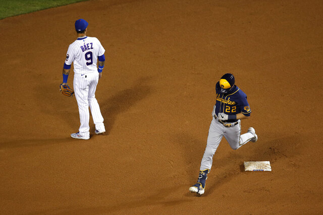 Milwaukee Brewers' Christian Yelich (22) rounds second base past Chicago Cubs shortstop Javier Baez (9) after hitting a three run home run during the sixth inning of a baseball game Friday, Aug. 14, 2020, in Chicago. (AP Photo/Jeff Haynes)