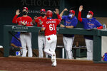 Texas Rangers' Robinson Chirinos (61) celebrates with coaching staff Don Wakamatsu, from left rear, manager Chris Woodward, Julio Rangel, and Hector Ortiz after Chirinos scored in the fourth inning of a baseball game against the Los Angeles Angels in Arlington, Texas, Friday, Aug. 7, 2020. (AP Photo/Tony Gutierrez)