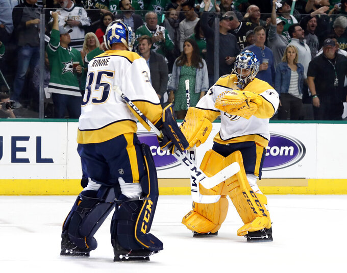 FILE - In this April 17, 2019, file photo, Nashville Predators' Pekka Rinne (35) greets Juuse Saros, right, as Rinne leaves the game after giving up four goals to the Dallas Stars in the first period of Game 4 in an NHL hockey first-round playoff series in Dallas. The NHL's pause has the clock ticking on the career of a former Vezina Trophy winner and four-time finalist with Rinne turning 38 in November.(AP Photo/Tony Gutierrez, File)