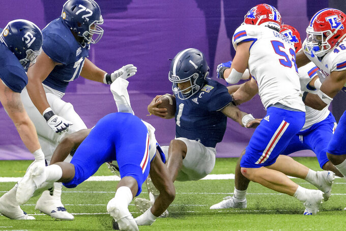 Georgia Southern quarterback Shai Werts (1) scores a touchdown against Louisiana Tech linebacker Tyler Grubbs (52) during the New Orleans Bowl NCAA college football game in New Orleans, Wednesday, Dec. 23, 2020. (AP Photo/Matthew Hinton)