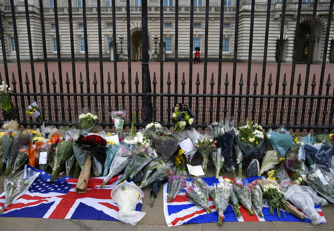 Flowers and other items are left by the public outside Buckingham Palace in London, Friday, April 9, 2021. Buckingham Palace officials say Prince Philip, the husband of Queen Elizabeth II, has died. He was 99. Philip spent a month in hospital earlier this year before being released on March 16 to return to Windsor Castle. (AP Photo/Alberto Pezzali)