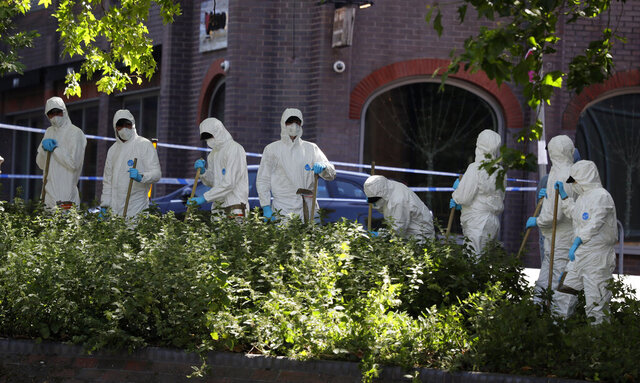 Police forensic officers search near the scene of a fatal multiple stabbing attack in Forbury Gardens, central Reading, England, Monday June 22, 2020. The English town of Reading is mourning for three people stabbed to death on Saturday in what is being treated as a terror attack. Residents gathered for a moment of silence Monday as police questioned the suspected lone wolf attacker. (AP Photo/Kirsty Wigglesworth)