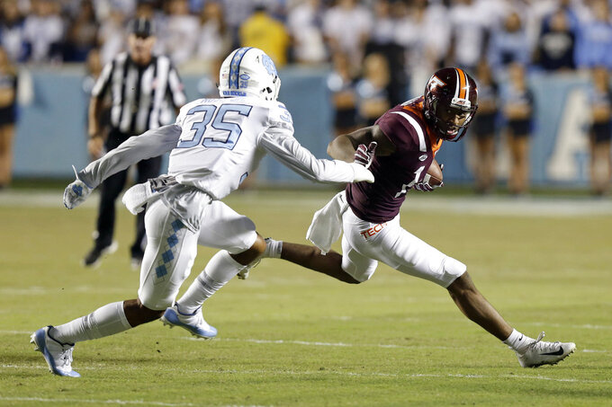 North Carolina's Greg Ross (35) chases Virginia Tech's Damon Hazelton during the first half of an NCAA college football game in Chapel Hill, N.C., Saturday, Oct. 13, 2018. (AP Photo/Gerry Broome)