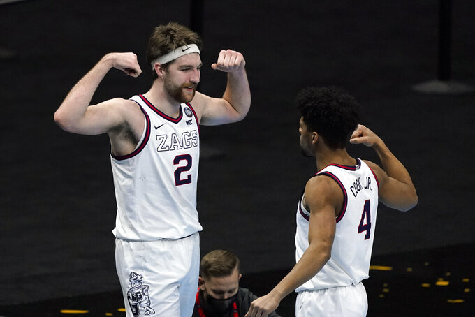 Gonzaga forward Drew Timme (2) celebrates with teammate guard Aaron Cook (4) after making a basket during the second half of a men's Final Four NCAA college basketball tournament semifinal game against UCLA, Saturday, April 3, 2021, at Lucas Oil Stadium in Indianapolis. (AP Photo/Darron Cummings)