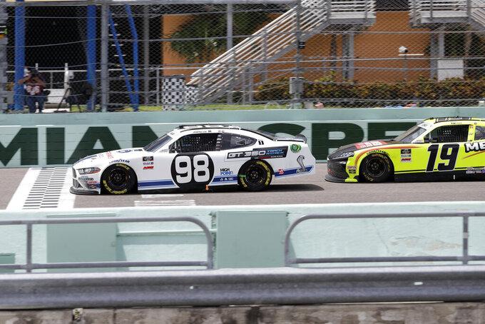 Chase Briscoe (98) crosses the finish line ahead of Brandon Jones (19) to win a NASCAR Xfinity Series auto race Sunday, June 14, 2020, in Homestead, Fla. (AP Photo/Wilfredo Lee)