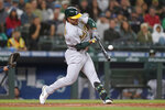 Oakland Athletics' Ramon Laureano hits a single to score Matt Chapman during the eighth inning of athe team's baseball game against the Seattle Mariners, Thursday, July 22, 2021, in Seattle. (AP Photo/Ted S. Warren)
