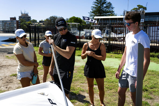 """This photo provided by SailGP shows Australia SailGP Team host women's selection camp from left to right Lisa Darmanin, Natasha Bryant, skipper Tom Slingsby, center, in Sydney, Australia on Feb. 5, 2021. Slingsby said. """"There's a lot of training ahead. We've seen some amazing male sailors who have been dropped out of SailGP because they just couldn't keep up. By no means is it going to be easy, but I just think it's great to give them the opportunity for them to come and live and train with team and see what it's all about and then if they're good enough, they'll make it."""" (Beau Outteridge/SailGP via AP)"""