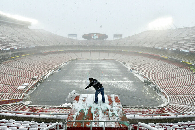 FILE - In this Jan. 12, 2019, file photo, Kyle Haraugh, of NFL Films, clears snow from a camera location at Arrowhead Stadium before an NFL divisional football playoff game between the Kansas City Chiefs and the Indianapolis Colts, in Kansas City, Mo.  The Chiefs began to lay new sod inside Arrowhead Stadium on Wednesday, Jan. 16, after much of the field was torn up in the divisional round. Heavy snow that began last Friday and stopped just before kickoff left parts of the field mushy, particularly between the hash marks and along the sidelines.  Those areas and the south end zone were getting fresh sod.  (AP Photo/Ed Zurga, File)