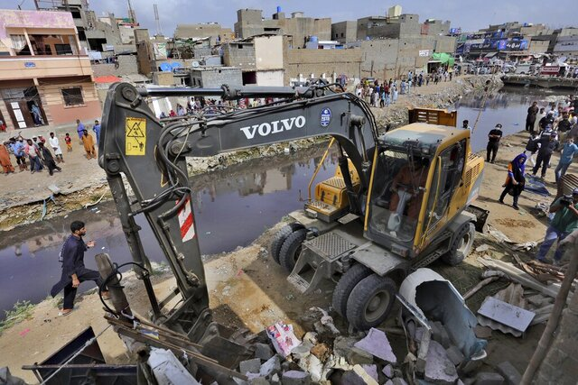 Local authorities use heavy machinery to demolish illegal construction alongside a drainage canal which saw flooding last week due to heavy monsoon rains, in Karachi, Pakistan, Wednesday, Sept. 2, 2020. Flash floods triggered by heavy rains killed some people and damaged scores of houses in Pakistan's scenic northwestern Swat Valley, a spokesman said Wednesday, as rescuers assisted residents in the port city of Karachi where last week's rains wreaked havoc that killed dozens. (AP Photo/Fareed Khan)
