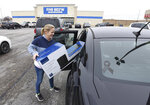 Gena Johnson of Maceo puts a sound-bar system into her car that she got a good deal on while shopping on Black Friday at Best Buy in Owensboro, Ky., on Friday, Nov. 29, 2019. (Alan Warren/The Messenger-Inquirer via AP)