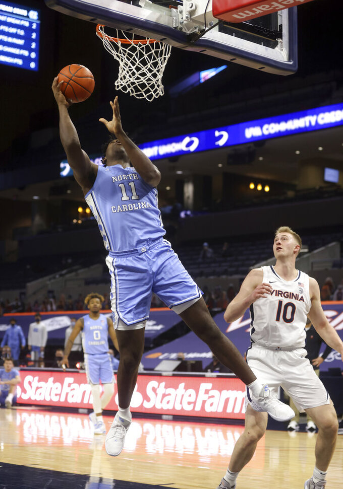 North Carolina forward Day'Ron Sharpe (11) shoots next to Virginia forward Sam Hauser (10) during an NCAA college basketball game Saturday, Feb. 13, 2021, in Charlottesville, Va. (Andrew Shurtleff/The Daily Progress via AP, Pool)
