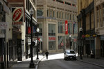 A passerby walks along a nearly empty street in the Downtown Crossing neighborhood of Boston, Tuesday, March 24, 2020. Many people are working from home in the state while many businesses have closed indefinitely out of concern about the spread of the coronavirus. (AP Photo/Steven Senne)
