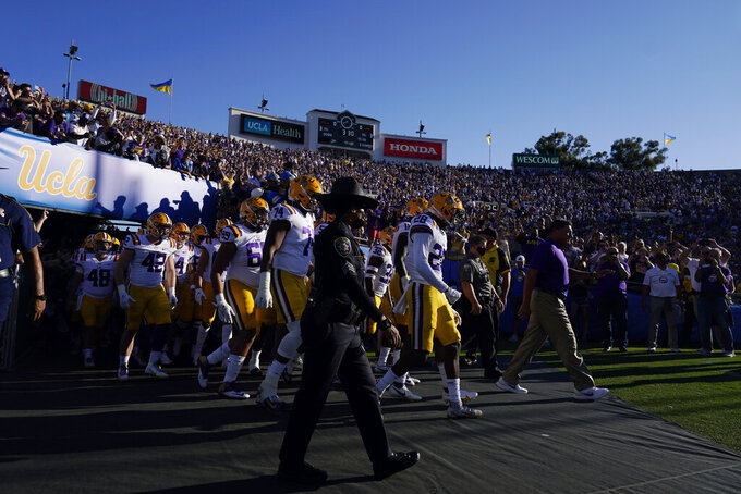 LSU coach Ed Orgeron, middle right, leads his team onto the field before an NCAA college football game against UCLA on Saturday, Sept. 4, 2021, in Pasadena, Calif. (AP Photo/Marcio Jose Sanchez)