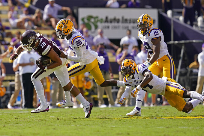 Mississippi State wide receiver Cameron Gardner (18) carries the ball against LSU's Keenen Dunn (26), safety Maurice Hampton Jr. (14) and linebacker Jabril Cox (19) in the first half an NCAA college football game in Baton Rouge, La., Saturday, Sept. 26, 2020. (AP Photo/Gerald Herbert)