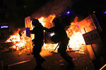 Policemen move as a police van runs over a burning barricade during clashes between protestors and police in Barcelona, Spain, Wednesday, Oct. 16, 2019. Spain's government said Wednesday it would do whatever it takes to stamp out violence in Catalonia, where clashes between regional independence supporters and police have injured more than 200 people in two days. (AP Photo/Bernat Armangue)