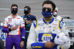 Denny Hamlin, left, Martin Truex, Jr., center, and Chase Elliott, right, put their hands to their heart during the national anthem prior to the NASCAR Cup Series auto race at Richmond International Raceway in Richmond, Va., Sunday, April 18, 2021. (AP Photo/Steve Helber)