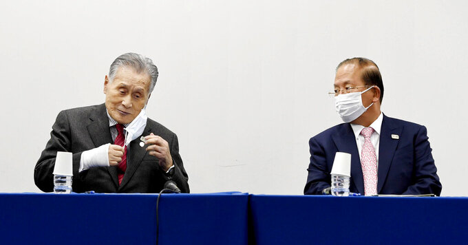 In this March 30, 2020, photo, Tokyo 2020 Organizing Committee President Yoshiro Mori, left, and Toshiro Muto, right, CEO of the Tokyo 2020 Organizing Committee, wear face masks during a news conference, in Tokyo Monday, March 30, 2020.  The countdown clock is ticking again for the Tokyo Olympics. They will be July 23 to Aug. 8, 2021. This seems light years away, but also small and insignificant compared to the worldwide fallout from the coronavirus. (Kyodo News via AP)