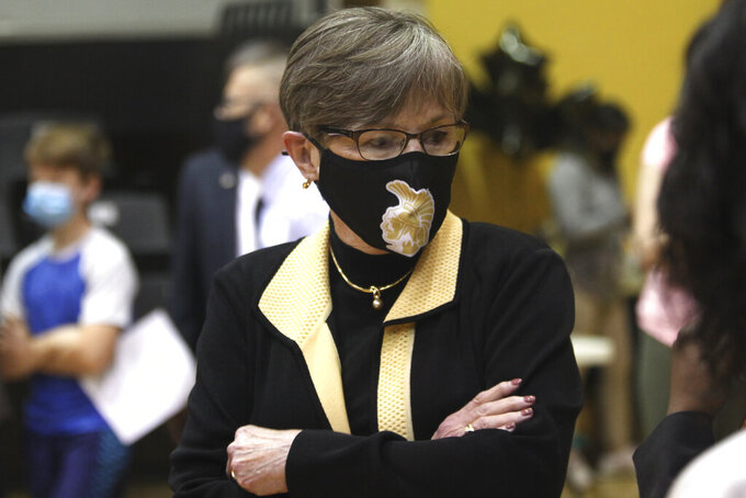 In this Monday, May 17, 2021, photo,  Kansas Gov. Laura Kelly tours a COVID-19 vaccination clinic for students aged 12 through 15 set up in a gym at Topeka High School in Topeka, Kan. The Democratic governor is under increasing pressure to end an extra $300 a week in benefits for unemployed workers, with critics of the aid arguing that businesses are having problems hiring enough workers because of it. (AP Photo/John Hanna)
