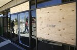 Several broken windows are boarded up at Phoenix Police Headquarters Friday, May 29, in Phoenix, after being broken during a demonstration protesting the death of George Floyd, a handcuffed black man who died in police custody with much of the arrest captured on video of a Minneapolis police officer kneeling on the neck of Floyd. (AP Photo/Ross D. Franklin)