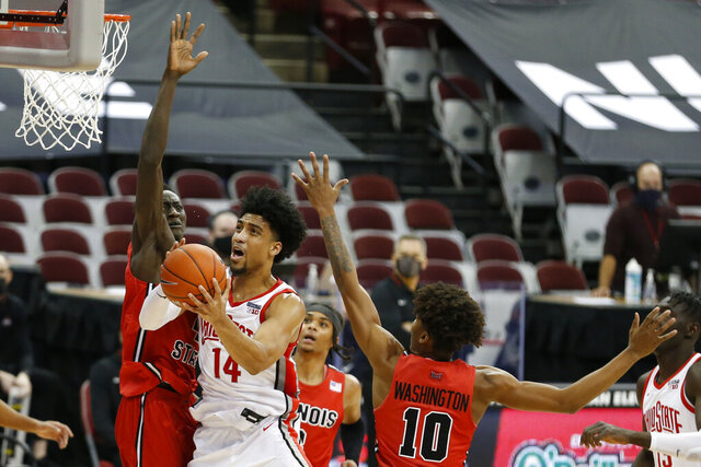 Ohio State's Justice Sueing, center, tries to shoot over Illinois State's Abdou Ndiaye, left, during the second half of an NCAA college basketball game Wednesday, Nov. 25, 2020, in Columbus, Ohio. Ohio State beat Illinois State 94-67. (AP Photo/Jay LaPrete)