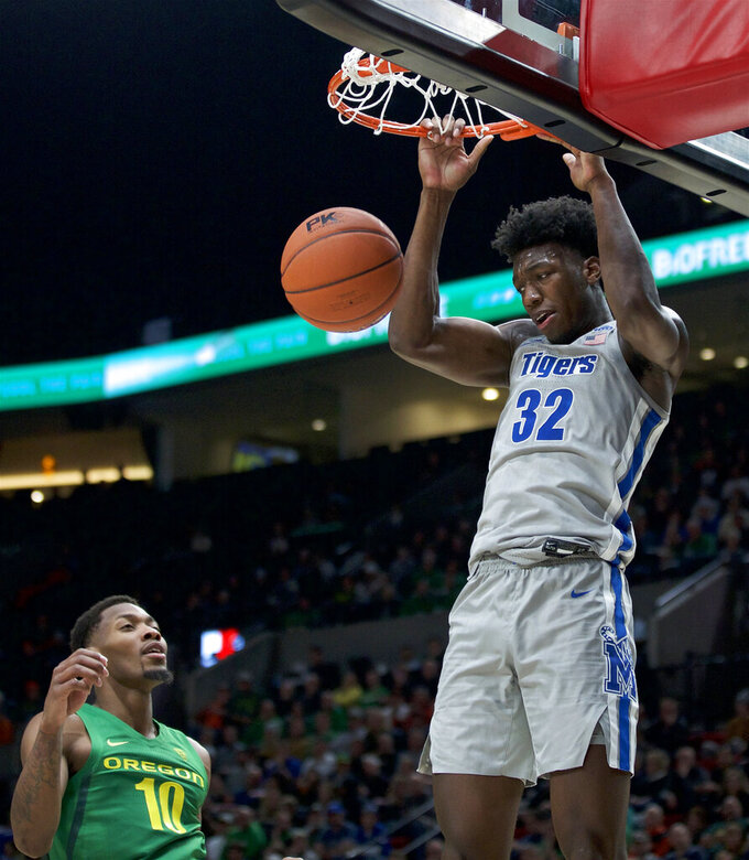 Memphis center James Wiseman dunks next to Oregon forward Shakur Juiston during the second half of an NCAA college basketball game in Portland, Ore., Tuesday, Nov. 12, 2019. Oregon won 82-74. (AP Photo/Craig Mitchelldyer)