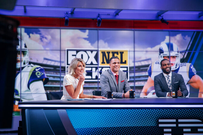 Charissa Thompson, left, Tony Gonzalez, center, and Michael Vick discuss NFL topics on the set of Fox NFL Kickoff during a 2019 show. The pregame show, like those on other networks, have had their challenges this year due to the coronavirus pandemic.(Lily Hernandez/FOX NFL Kickoff via AP)