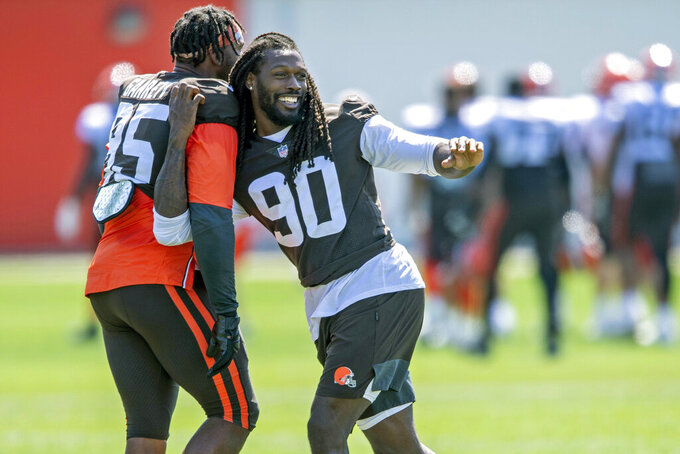 FILE - In this Aug. 4, 2021, file photo, Cleveland Browns defensive linemen Jadeveon Clowney, right, goofs around with defensive linemen Myles Garrett (95) during an NFL football practice in Berea, Ohio. The Browns will have at least seven new starters on defense — maybe more depending on the package they're in — when the season kicks off Sunday against the Kansas City Chiefs at Arrowhead. (AP Photo/David Dermer, File)
