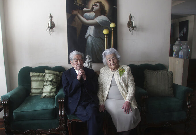 Married couple Julio Mora Tapia, 110, and Waldramina Quinteros, 104, both retired teachers, pose for a photo at their home in Quito, Ecuador, Friday, Aug. 28, 2020. The couple is recognized by the Guinness World Records as the oldest married couple in the world, because of their ages. They have been married for 79 years. (AP Photo/Dolores Ochoa)