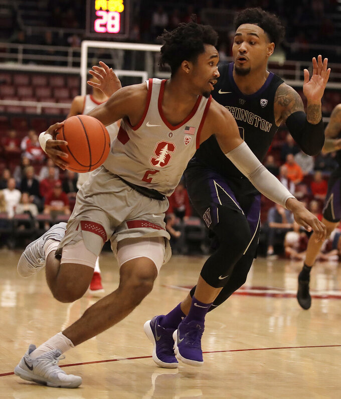 Stanford's Bryce Wills, left, drives the ball against Washington's David Crisp in the first half of an NCAA college basketball game Sunday, March 3, 2019, in Stanford, Calif. (AP Photo/Ben Margot)