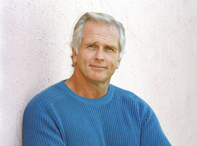 "FILE - This Dec. 28, 1987 file photo shows former ""Tarzan"" actor Ron Ely during an interview in Los Angeles. A woman was killed at Ely's Southern California home and sheriff's deputies fatally shot a suspect on the property, authorities said Wednesday, Oct. 16, 2019. A Santa Barbara County sheriff's office statement does not identify any of those involved but notes that a disabled elderly man living at the home was taken to a hospital for evaluation. The deaths occurred Tuesday night in Hope Ranch, a suburb of luxury homes outside Santa Barbara. (AP Photo/Reed Saxon, File)"
