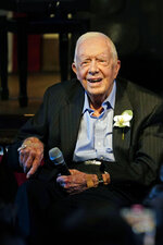 Former President Jimmy Carter smiles as his wife former first lady Rosalynn Carter speaks during a reception to celebrate their 75th wedding anniversary Saturday, July 10, 2021, in Plains, Ga.. (AP Photo/John Bazemore, Pool)