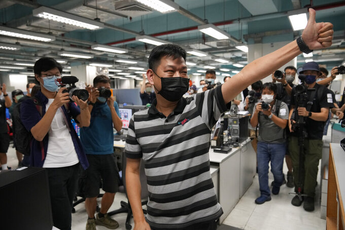 FILE - In this June 23, 2021, file photo, Lam Man-chung, center, executive editor-in-chief of Apple Daily, gestures at the headquarters before the newspaper stop publishing in Hong Kong. Hong Kong national security police on Wednesday, July 21, 2021, arrested Lam, weeks after the paper was forced to close after authorities froze its assets. (AP Photo/Kin Cheung, File)