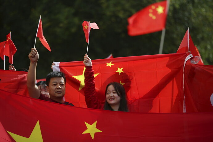 """FILE - In this Aug. 17, 2019, file photo, pro-China counter-protesters hold Chinese flags during an anti-extradition rally for Hong Kong in Vancouver. Governments around the world are taking a cautious approach to responding to the protests roiling Hong Kong. With the notable exception of Taiwan, cautious comments from a handful of governments fall short of support for the demonstrators. They are so mild that even the word """"protest"""" itself was left out of the joint EU-Canada statement that was the most recent to infuriate the Chinese government. Most are unwilling to risk that fury at all, showing China's deep influence around the world. (Darryl Dyck/The Canadian Press via AP, File)"""