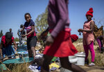 Zimbabwean women and girls wash their clothes next to a lake on the outskirts of the capital Harare, Zimbabwe Sunday, Sept. 8, 2019. Former president Robert Mugabe, who enjoyed strong backing from Zimbabwe's people after taking over in 1980 but whose support waned following decades of repression, economic mismanagement and allegations of election-rigging, is expected to be buried next Sunday, state media reported. (AP Photo/Ben Curtis)