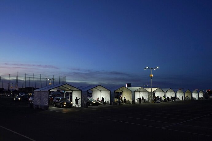 Several tents are set up so people who have registered can get their COVID-19 vaccinations as they drive-thru the parking lot of the State Farm Stadium, Tuesday, Jan. 12, 2021, in Glendale, Ariz. The Arizona Cardinals' stadium opened as a vaccination site Monday that will be a 24-7 operation. (AP Photo/Ross D. Franklin)