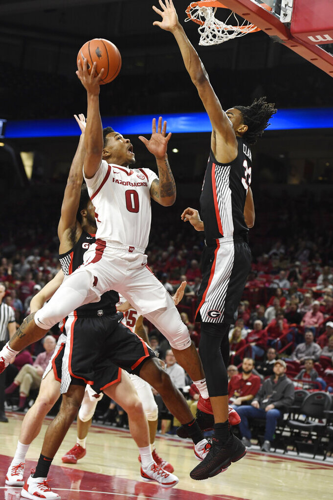 Arkansas guard Desi Sills (0) drives past Georgia defender Nicolas Claxton (33) during the first half of an NCAA college basketball game, Tuesday, Jan.29, 2019 in Fayetteville, Ark. (AP Photo/Michael Woods)
