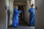 In this photo provided by the Alfred-Wegener-Institut and taken on May 6, 2020, Anna-Lena Bohlen, right and Eberhard Kolhberg enter the room of a MOSAiC scientist to take a coronavirus test, in Bremerhaven, Germany. They prepared for icy cold and trained to watch for polar bears, but a pandemic just wasn't part of the program. Now dozens of scientists are sitting in quarantine, waiting for permission to sail forth and capture a crucial moment in the polar calendar that's essential to their year-long Arctic research mission. (Alfred-Wegener-Institut via AP)