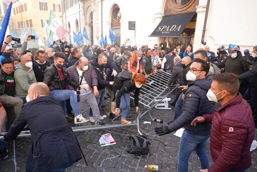 Demonstrators step on barriers set up by Italian Police during a protest by Restaurant owners and workers outside the Lower Chamber in Rome, Tuesday, April 6, 2021. Demonstrators demanded to reopen their business and protested against restrictive measures by the Italian Government to cope with the surge of COVID-19 cases. (AP Photo/Andrew Medichini)