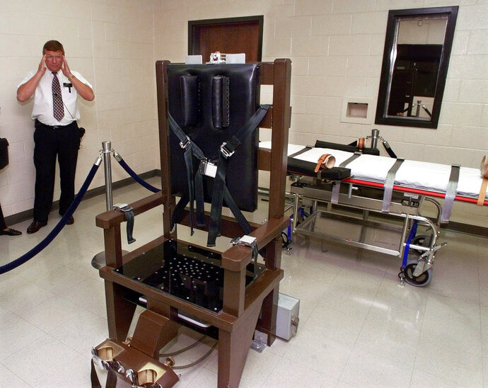 FILE - In this Oct. 13, 1999, file photo, Ricky Bell, then the warden at Riverbend Maximum Security Institution in Nashville, Tenn., gives a tour of the prison's execution chamber. Attorneys for Tennessee death row inmate Edmund Zagorski on Wednesday, Oct. 10, 2018, asked a federal court to force the state to use the electric chair to execute him, rather than lethal injection. The court battle over his Thursday execution played out over a solemn background in which prison staff and volunteers said the death of the well liked inmate will leave an impact. (AP Photo/Mark Humphrey, File)