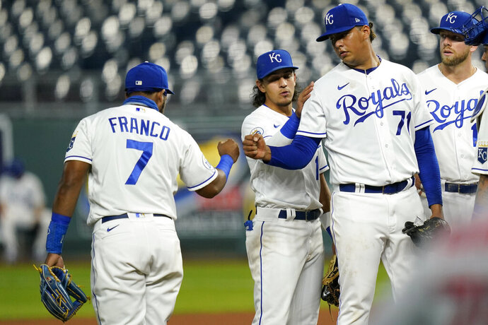Kansas City Royals starting pitcher Carlos Hernandez (71) fist-bumps third baseman Maikel Franco (7) before leaving in the fourth inning of a baseball game against the St. Louis Cardinals at Kauffman Stadium in Kansas City, Mo., Monday, Sept. 21, 2020. (AP Photo/Orlin Wagner)