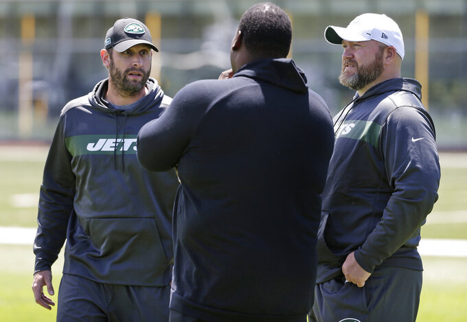 FILE - In this June 11, 2019, file photo, New York Jets general manager Joe Douglas, right, and coach Adam Gase, left, speak to former offensive lineman Damien Woody during a practice at the team's NFL football training facility in Florham Park, N.J. Gone are coach Todd Bowles and general manager Mike Maccagnan, replaced by Gase and Douglas--two buddies from their days in Chicago. (AP Photo/Seth Wenig, File)
